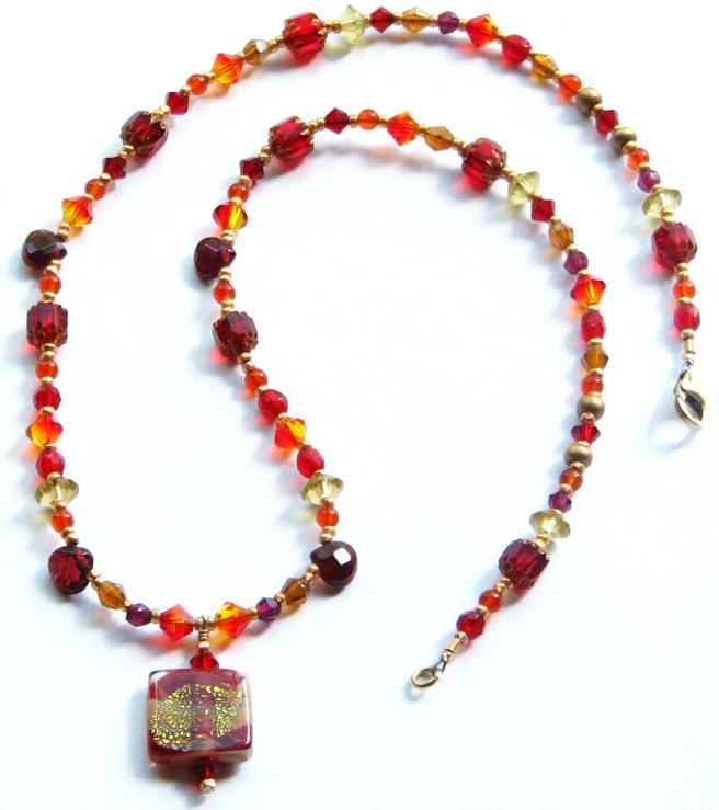 lampworked glass pendant with garnets, carnelain, Swarovski crystals