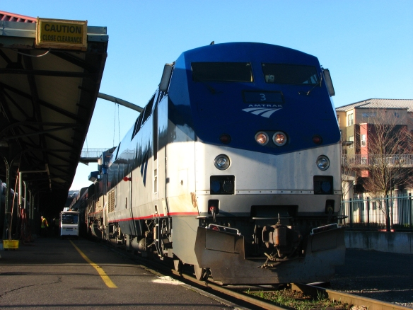 Amtrak train in front of a station house.