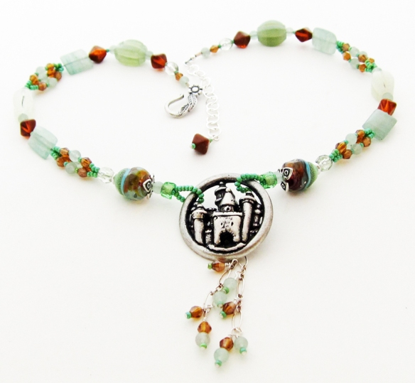 green necklace with castle pendant and chain dangle