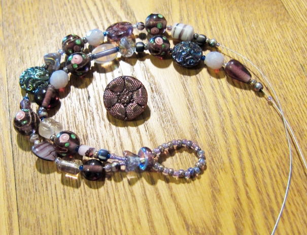 two strands of purple glass beads before the clasp is added