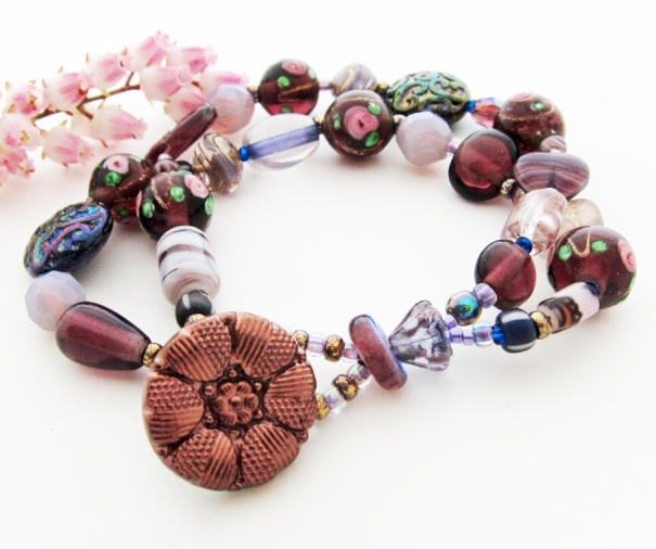 two strand purple beaded bracelet with purple vintage glass button clasp.
