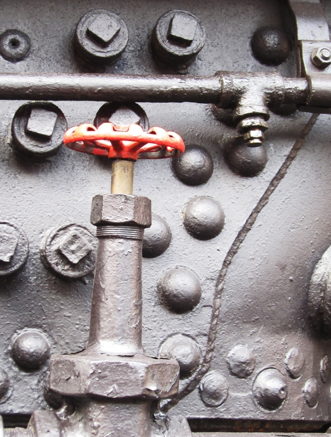 red valve on the side of an old black steam engine