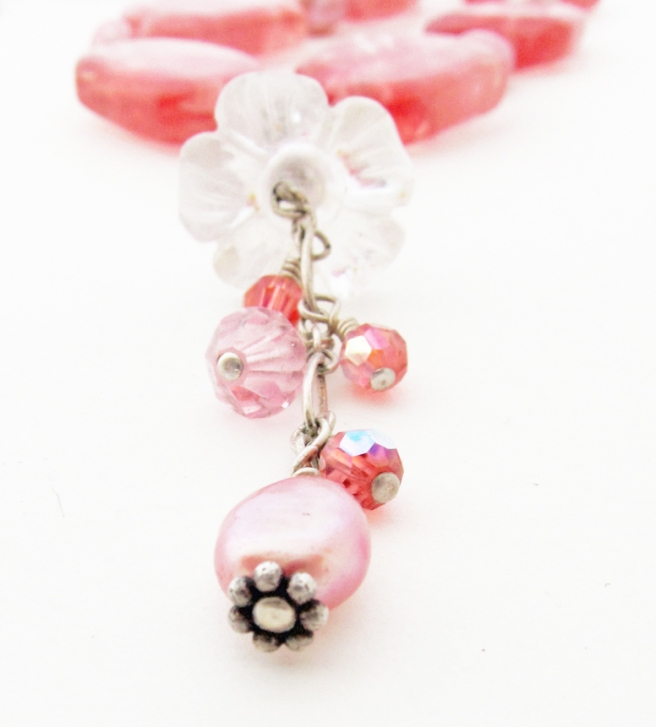 carved rose quartz flower pendant on a pink handmade necklace.