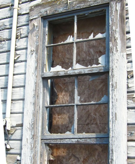 broken window, boarded over in an abandoned warehouse